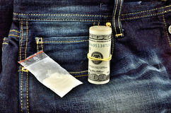 White powder and dollars on jeans Royalty Free Stock Photo