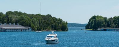 White power boat and boathouses in panoramic format. White power boat and boathouses on Lake Charlevoix in Upper Michigan royalty free stock photos