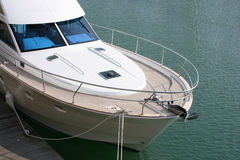 White powerboat. White luxury powerboat moored against wooden jetty Stock Images