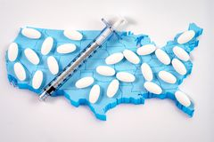 White prescription pills and syringe on map of America background Stock Images
