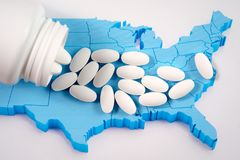 White prescription pills spilling from medicine bottle over map of America. White prescription pharmaceutical pills spilling from medicine bottle on American map royalty free stock photography