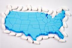 White prescription pills surrounding map of America. White prescription pharmaceutical pills surrounding American map background stock photos