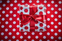 White present box with tied ribbon on polka-dot red fabric celeb Royalty Free Stock Photography