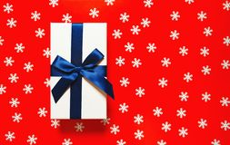 Free White Present Box With Dark Blue Ribbon And Bow On Red Background With Decorative Snowflakes. Christmas Gift Concept. Festive And Stock Images - 162494924