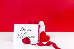 White gift box and be my valentine card decorated with red ribbon and heart shape fabric on red background stock photography