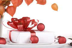 White present with red ribbons on a dinner plate, Royalty Free Stock Image