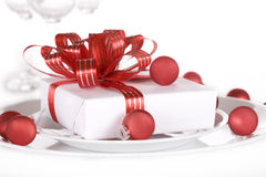White present with red ribbons on a dinner plate Royalty Free Stock Photo