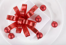 White present with red ribbons on a dinner plate Stock Photos