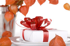White present with red ribbons on a dinner plate Royalty Free Stock Photography