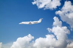 White Private Jet Business Jet Flies Against Backdrop Of Beautiful White Clouds On Blue Sky Royalty Free Stock Photography