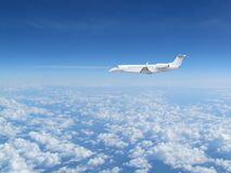 White Private Jet Business Jet Flies Against Backdrop Of Beautiful White Clouds On Blue Sky Stock Photos