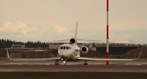 Private jet. White private jet waiting in takeoff line in the evening just before sunset royalty free stock image