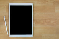 White pro tablet computer with blank black screen next to white Royalty Free Stock Images