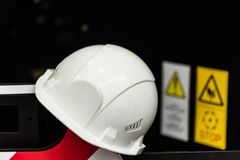 Safety helmet against industrial background. White protective helmet or hard hat against industrial background at machinery plant. Headpiece as a mean of safety Stock Image