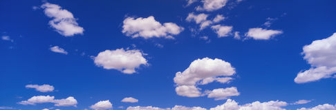 White puffy clouds and blue sky. This is an image of a blue sky with white puffy clouds scattered throughout Stock Photography