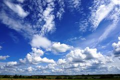 White puffy clouds in blue sky, agricultural landscape Stock Images