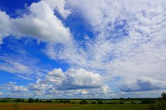 White puffy clouds in blue sky, agricultural landscape Stock Photography