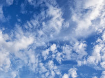 White, puffy clouds in blue sky with jet and con trail. White, puffy clouds in blue sky with jet and it's con trail tracing between the clouds Stock Images