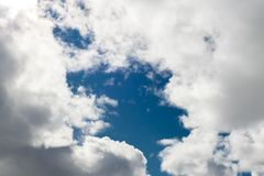 White puffy clouds with blue sky in the middle Stock Photography