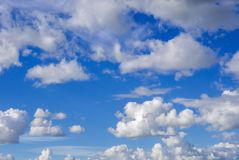 White puffy clouds on a bright blue sky. A background of White puffy clouds against a clear blue sky Stock Photography