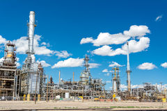 White puffy clouds over an oil refinery Stock Photos