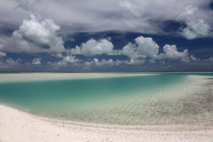 White puffy clouds over turquoise lagoon water. Royalty Free Stock Image