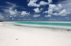 White puffy clouds over turquoise lagoon water. Royalty Free Stock Photography