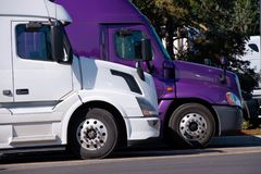 White and purple big rigs semi trucks stand on truck stop side b Stock Photo