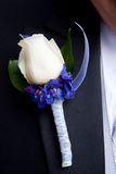 White and Purple Boutonniere. A white and purple boutonniere on a tuxedo Royalty Free Stock Images