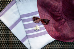 A white and purple color Turkish peshtemal / towel, sunglasses, white seashells and straw hat on rattan lounger as background. Stock Photography