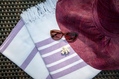 A white and purple color Turkish peshtemal / towel, sunglasses, white seashells and straw hat on rattan lounger as background. Stock Photos