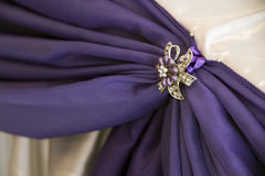 White and purple drapes with brooches Stock Image