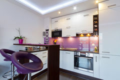 White and purple kitchen with spotlights. Modern white and purple kitchen interior with spotlights Stock Images