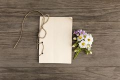 White and purple potatoes flowers with handmade craft notebook on old grunge wooden background. Top view. Minimalistic stock photography