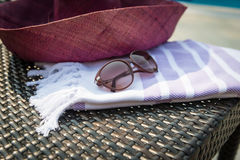 A white and purple Turkish towel, sunglasses and straw hat on rattan lounger with a blue swimming pool as background. Royalty Free Stock Photography