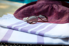 A white and purple Turkish towel, sunglasses and straw hat on rattan lounger with a blue swimming pool as background. Royalty Free Stock Photo