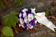White and purple wedding bouquet with eustomas. Colorful wedding bouquet with eustomas laying on the ctone Stock Photography