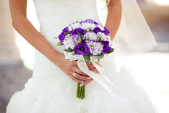White and purple wedding bouquet with eustomas in hands. Colorful wedding bouquet with eustomas  in bride's hands Royalty Free Stock Images