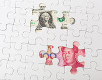 White puzzle with American dollar and chinese yuan. Close up Stock Photo