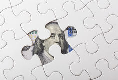 White puzzle with American dollar. Close up Stock Photos