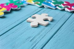 White puzzle on color wooden background. Concept of autism Royalty Free Stock Image