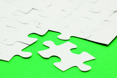 White puzzle on green surface Royalty Free Stock Photo