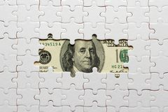 White puzzle on hundred dollars banknotes royalty free stock photos