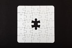 White puzzle with one missing piece on black background. Problem concept. Top view. Flat lay Stock Photography