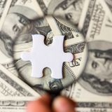 White puzzle piece and magnifying glass on a dollar bills background stock image