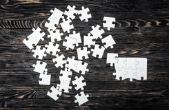 White puzzle pieces on dark table Royalty Free Stock Photography