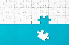 White puzzle pieces and place on blue background. Stock Photo