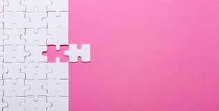 White puzzle on pink background. Missing piece stock images