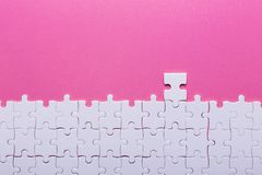 White puzzle on pink background. Top view stock photography