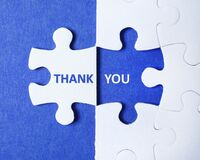 White puzzle with separated piece and phrase THANK YOU on background, top view